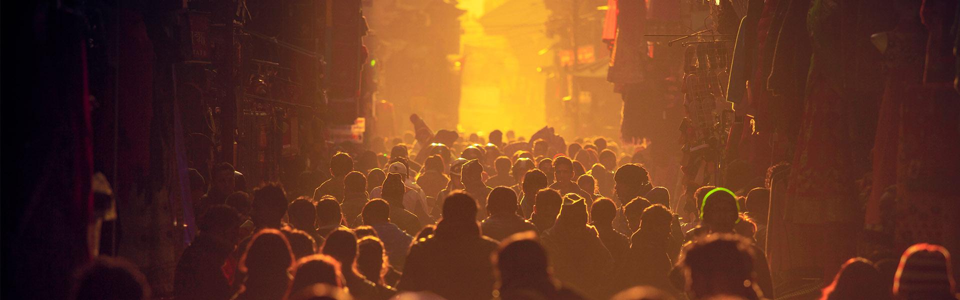 Crowded people backlit walking in street in yellow glow