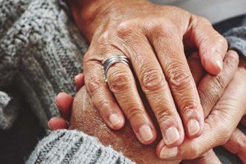 Female carer holding hands of senior man